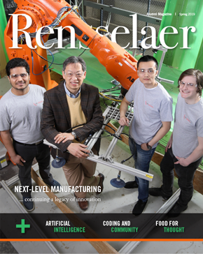 John Wen and team with robotic manufacturing arm in background