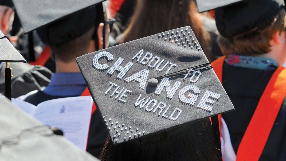 "Graduation cap with ""About to Change the World"" printed in white crystals"