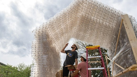 Students use empty plastic water bottles to construct a shelter