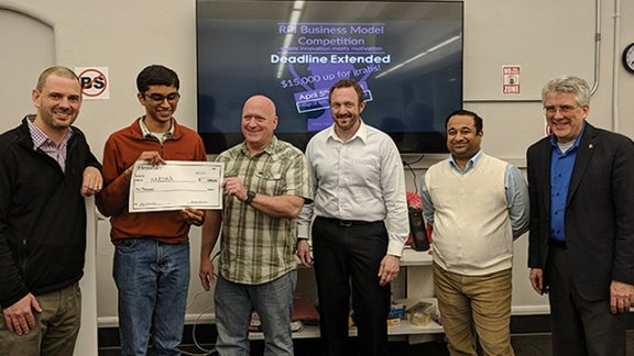 Clint Ballinger (holding check, center), Executive Entrepreneur in Residence at the Severino Center, presents the award to Kapila Chandramouli '18 of Kapshur Medical Devices (formerly HARSHA).