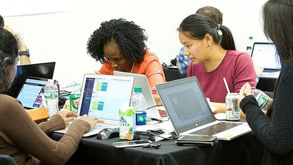 Group of students with laptops participating in the health hackathon