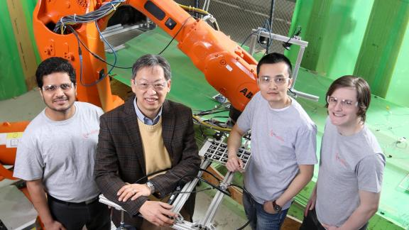 John Wen and team standing in front of robotic arm